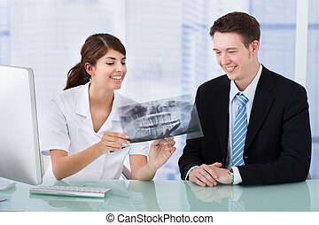 Dentist Showing Jaw Xray To Businessman In Clinic - Young...