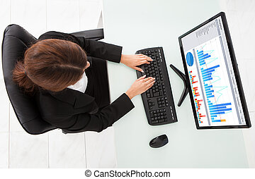 Businesswoman Making Financial Charts On Computer At Office...