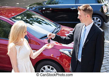 Salesman Handing Key To Woman By New Car - Young salesman...