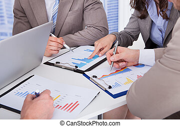 Business People Discussing Over Graph In Office