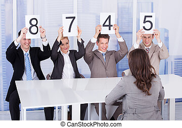 Business People Showing Score Cards In Front Of Female...