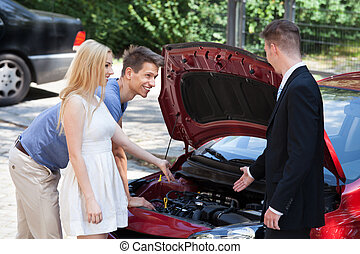 Salesman Showing New Car Engine To Couple