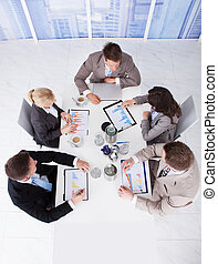 Business People Discussing On Graphs At Conference Table -...