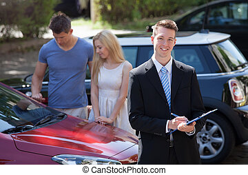 Salesman Writing On Clipboard With Couple Looking At Car