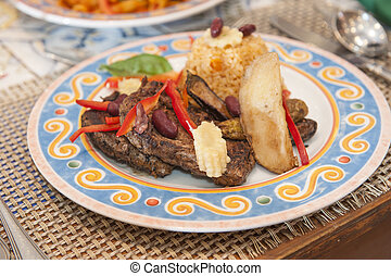 A la carte steak meal on patterned plate - Closeup detail of...