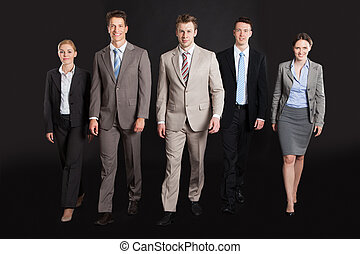 Confident Business People Walking Against Black Background -...
