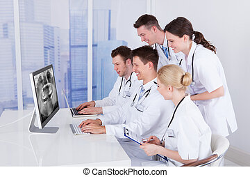 Dentists Examining Jaw Xray On Computer - Team of dentists...