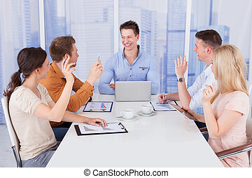 Colleagues Asking Question To Manager In Meeting -...