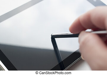 Close-up of woman working with stylus on digital tablet pc,