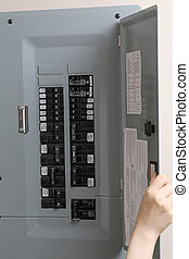 Woman checking automatic fuses at electrical control panel...