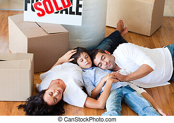 Family moving house sleeping on floor - happy family moving...