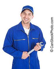 mecánico, en, azul, overol, tenencia, llave inglesa
