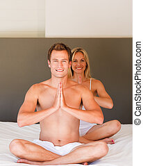 Young couple doing yoga moves on bed together