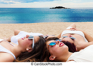 Grilfriends relaxing together on Carribean beach. - Portrait...