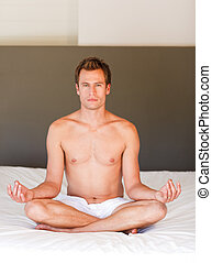 Young man doing yoga on bed