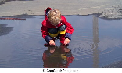 Childhood Fun - Blond boy looking at his reflection in pool...