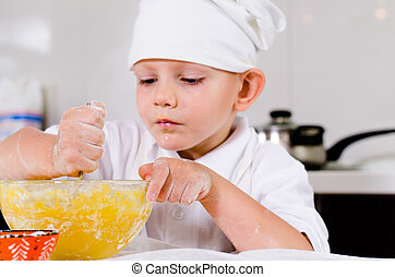 Small boy mixing ingredients for a cake in a bowl...