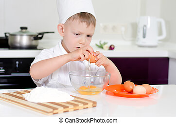 Young boy earning to be a chef breaking eggs into a mixing...