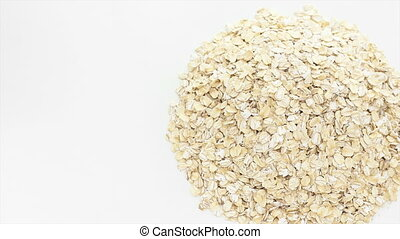 Raw oat rotating on the white table with white seamless...