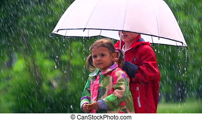 Raining Cats and Dogs - Kids standing with umbrella under...