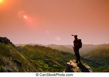 Man on mountain at dawn - Man on mountain at dawn in...