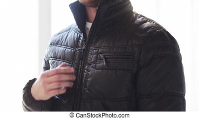 close up of man unzipping his black jacket at home -...