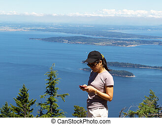 Mature woman trying to use her cell phone while outdoors...