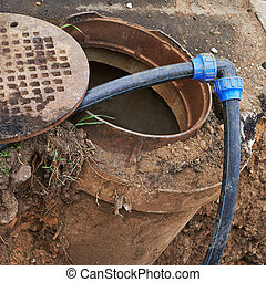 Cleaning equipment in a sewer manhole - Cleaning equipment...