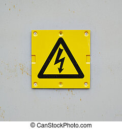 Yellow warning sign on a gray wall