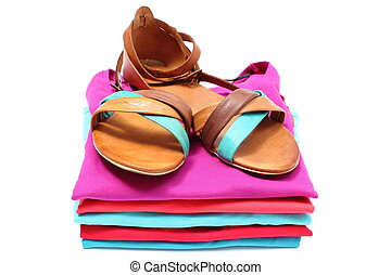 Woman sandals on pile of colorful clothes. White background...