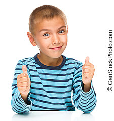 Portrait of a cute boy showing thumb up sign