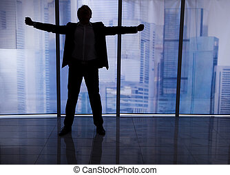 Businessman Standing Arms Outstretched By Office Window