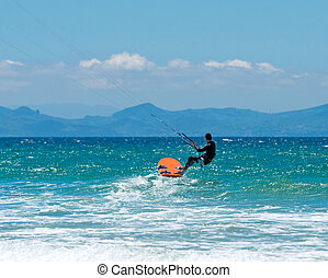 Kite surfing on a pristine beach - sportsman kite sergfer on...
