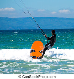 Kite surfing on a pristine beach - young sportsman kite...