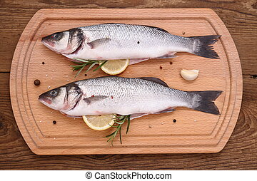 Two fresh moronidae fish on cutting board with ingredients,...