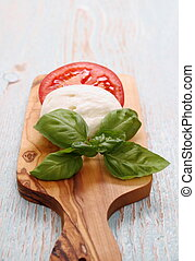 Basil leaf, mozzarella cheese and tomato slice, vertical