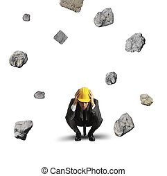 Frightened businessman under the storm of falling rocks