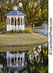 White Gazebo and Reflection - A white gazebo next to a lake