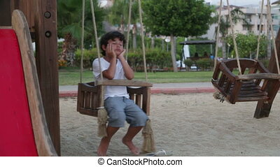 Lonely sad boy in playground - Sad boy swinging in the...