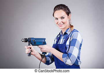 Smiling woman with drill