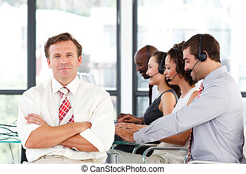 Senior leadership with crossed arms in a call center -...
