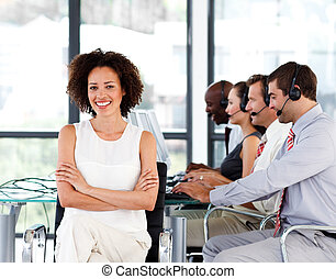 Smiling female manager working in a call center with her...