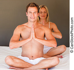 Two people doing yoga - Young woman and smiling man doing...