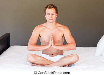 Young boy doing yoga on bed with clossed eyes - Attractive...