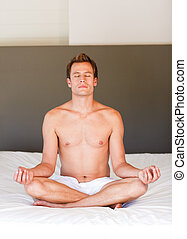 Handsome man doing meditation on bed - Handsome young man...