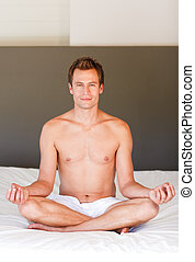 Handsome man meditating on bed