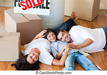 Smiling family in their new house lying on floor with boxes