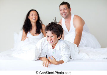 Family playing with his son in bed