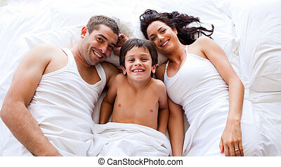 Family playing lying his son in bed