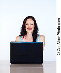 Woman working with a laptop smiling at the camera